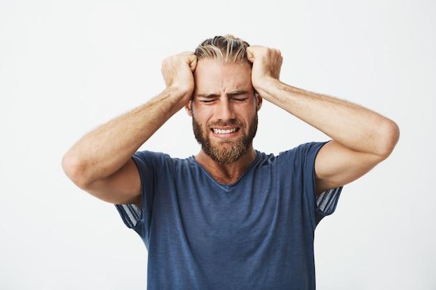Porträt des schönen nordischen kerls mit trendigem haarschnitt und bart, der kopf mit händen hält, die unter kopfschmerzen leiden