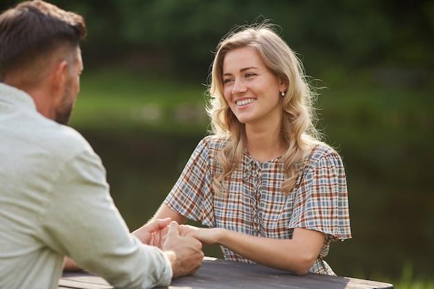 Porträt des schönen paares, das hände hält und einander mit liebe betrachtet, während am tisch im freien am see während des romantischen datums sitzt