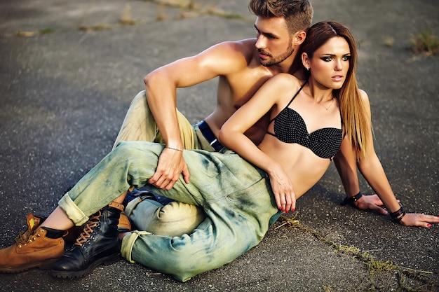 Porträt des schönen paares. sexy stilvolles blondes junges frauenmodell mit hellem make-up mit perfekter sonnengebadeter haut und hübschem muskulösem mann in den jeans draußen auf asphalthintergrund