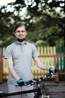 Porträt des schönen radfahrermanns, der draußen im warmen sommerabend gegen farbigen zaun steht
