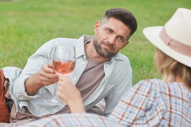 Porträt des schönen reifen mannes, der weinglas hält, während das picknick auf grünem gras während des romantischen datums im freien genießt