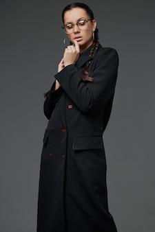 Porträt des schönen reizend hispanischen mädchens im langen schwarzen mantel