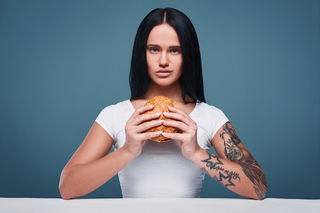 Porträt des schönen reizend tätowierungsmädchens, das hamburger hält