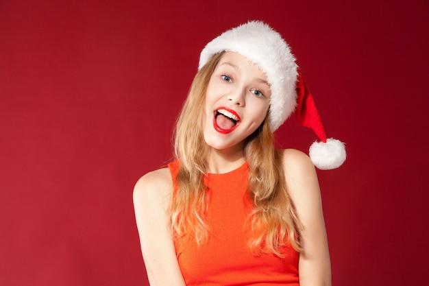 Porträt des schönen sexy mädchens, das weihnachtsmann-kleidung über rotem hintergrund trägt