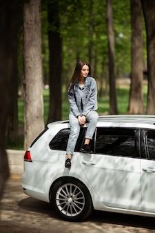 Porträt des schönen sexy modebrünettenfrauenmodells in der jeansjacke sitzend