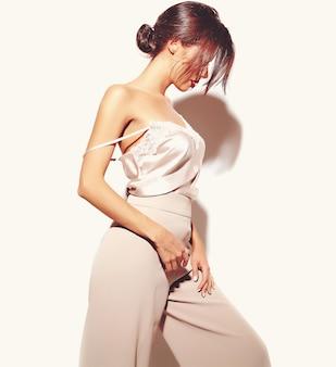 Porträt des schönen sinnlichen brunettefrauenmädchens in der eleganten weißen klassischen kleidung und in den weiten hosen auf weißem hintergrund