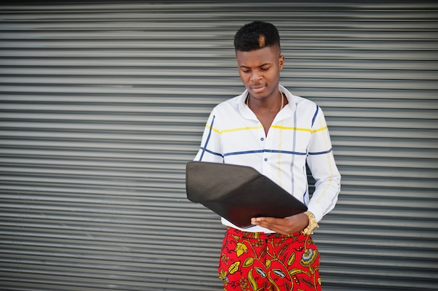 Porträt des schönen stilvollen afroamerikanischen modellmannes in den roten throusern und im weißen hemd mit laptop auf händen gegen stahlverschlusshintergrund.