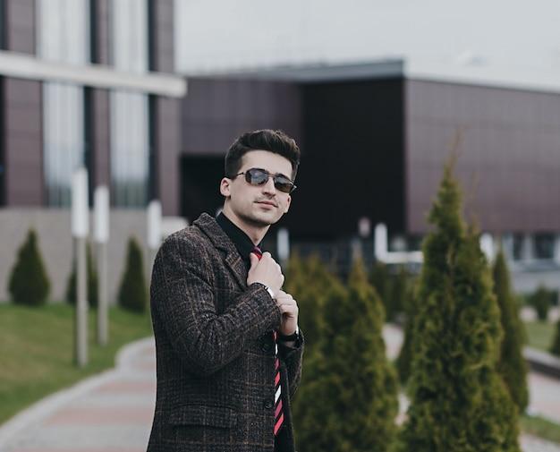 Porträt des schönen stilvollen geschäftsmannmodells. mann im eleganten mantel gekleidet. mode-mann, der auf der straße aufwirft