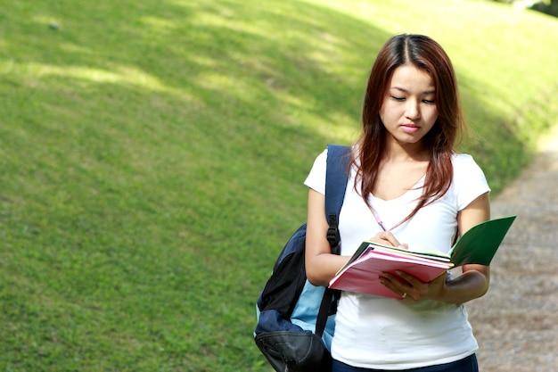 Porträt des schönen studenten, der am college-park studiert