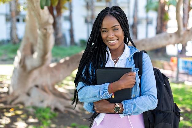 Porträt des schönen studentenafromädchens, das kamera betrachtet.