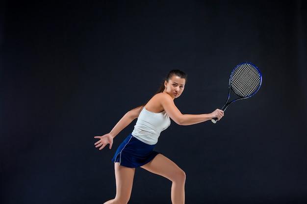Porträt des schönen tennisspielers mit einem schläger an der dunklen wand