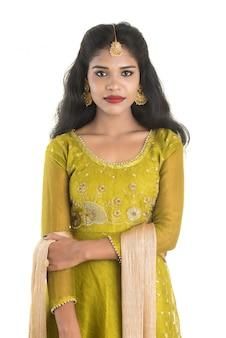 Porträt des schönen traditionellen indischen mädchens, das auf weißem raum aufwirft.