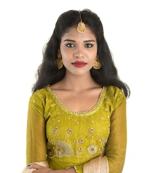 Porträt des schönen traditionellen indischen mädchens, das auf weißer wand aufwirft