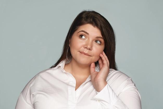 Porträt des schönen übergewichtigen jungen weiblichen angestellten, der weißes hemd und runde ohrringe trägt, die nach oben schauen und lippe beißen, nachdenklichen ausdruck haben und denken, was gesundes essen zum mittagessen essen