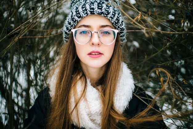 Porträt des schönen und stilvollen brunettemädchens in den gläsern im winterpark.