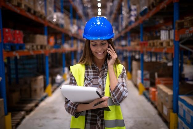 Porträt des schönen weiblichen lagerarbeiters, der konversation auf handy in großem speicherverteilungszentrum hat