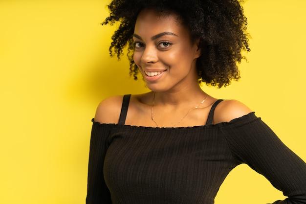 Porträt des schönen weiblichen modells des afroamerikaners lächelnd.