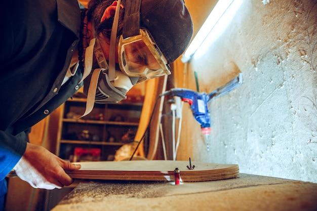 Porträt des schönen zimmermanns, der mit hölzernem schlittschuh an werkstatt arbeitet, profilansicht