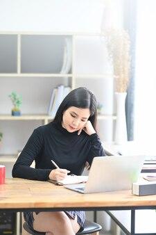 Porträt des schönheitsdesigners, der im kreativen büro sitzt und mit laptop-computer arbeitet.