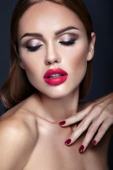 Porträt des schönheitsmodells mit abendmake-up und romantischer frisur. rote lippen