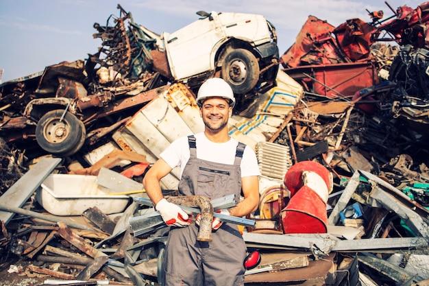 Porträt des schrottplatzarbeiters, der metallteile hält.