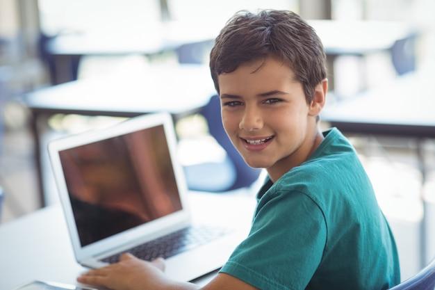 Porträt des schülers unter verwendung des laptops im klassenzimmer