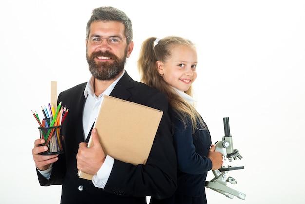 Porträt des schülerschulmädchens und des tutors mit schulmaterial. ernster lehrer. zurück zur schule.