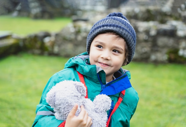 Porträt des schulkindes, das teddybär nimmt, erforschen mit seiner lerngeschichte