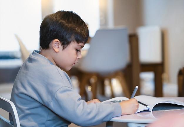 Porträt des schulkindes, der auf tisch sitzt, der hausaufgaben macht