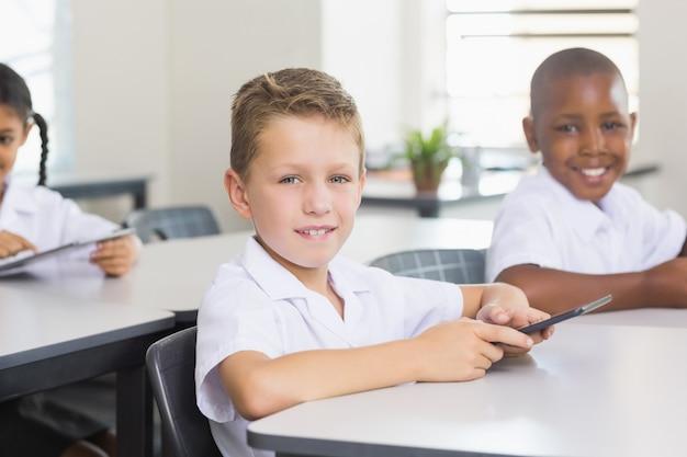 Porträt des schulkindes unter verwendung des mobiltelefons im klassenzimmer