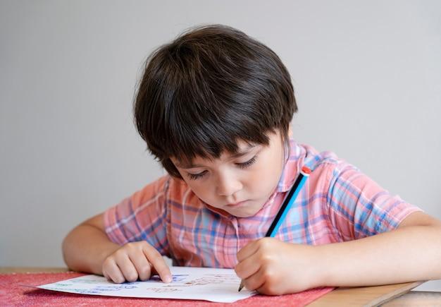 Porträt des schulkindjungen, der auf dem tisch sitzt, der hausaufgaben macht, glückliches kind, das bleistiftschreiben hält, ein junge, der auf weißem papier am tisch zeichnet, grundschule und homeschooling-konzept