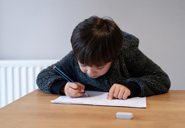 Porträt des schulkindjungen, der auf tisch sitzt, der hausaufgaben macht, glückliches kind, das bleistiftschreiben hält, ein junge, der englische wörter auf weißem papier schreibt, grundschule und homeschooling-konzept
