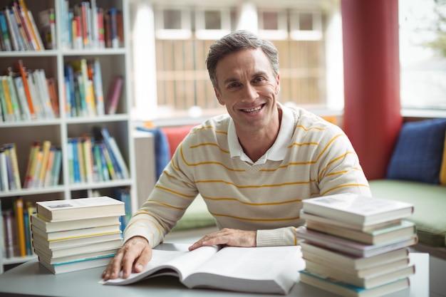 Porträt des schullehrers, der buch in der bibliothek liest