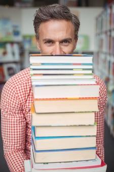 Porträt des schullehrers, der stapel bücher in der bibliothek hält