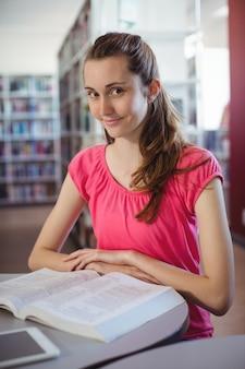 Porträt des schulmädchen-lesebuchs in der bibliothek