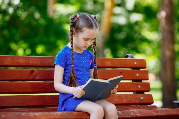 Porträt des schulmädchens auf einer bank, die buch liest. hintergrundstadtpark.