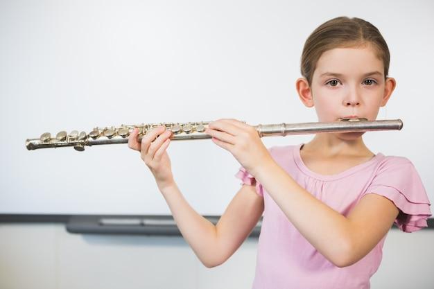 Porträt des schulmädchens, das flöte im klassenzimmer spielt