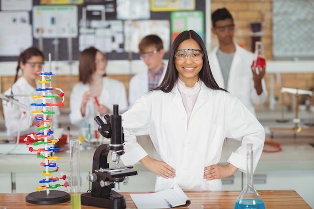 Porträt des schulmädchens, das mit hand auf hüfte im labor steht