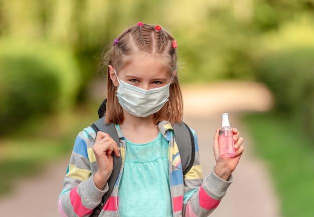Porträt des schulmädchens in der maske, die desinfektionsmittel auf natur hält
