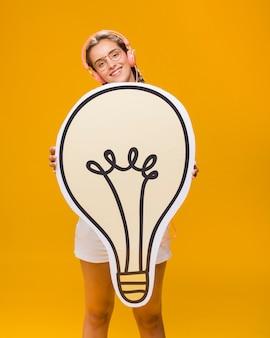 Porträt des schulmädchens mit großer glühlampe