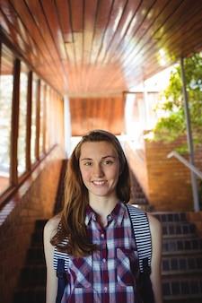 Porträt des schulmädchens zur schultasche, die nahe treppe steht