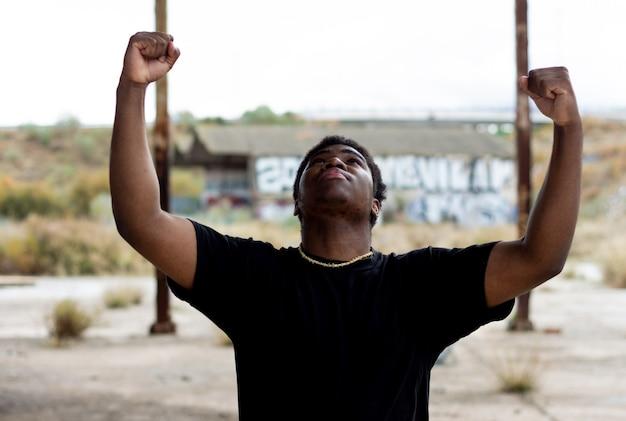 Porträt des schwarzen jungen, der seine arme hebt und den sieg feiert