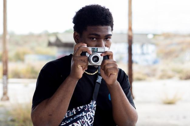 Porträt des schwarzen kerls, der ein bild mit einer weinlesekamera macht.