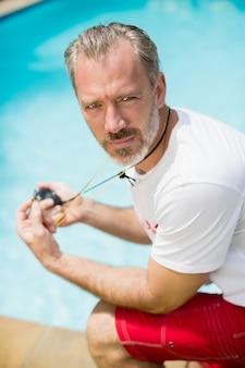 Porträt des schwimmtrainers, der stoppuhr nahe poolseite hält