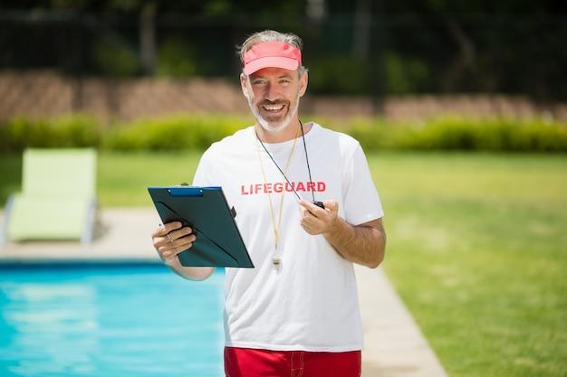 Porträt des schwimmtrainers, der stoppuhr und klemmbrett nahe am pool hält