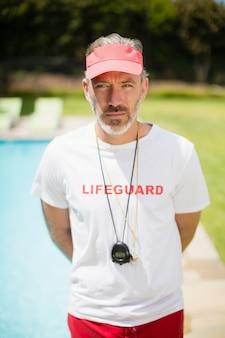 Porträt des schwimmtrainers mit stoppuhr, die nahe poolseite steht