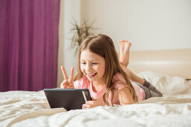 Porträt des sehr schönen kleinen mädchens, das in smartphone lächelt, selfie nimmt oder mit freunden auf videoanruf kommuniziert