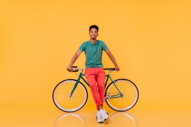 Porträt des selbstbewussten afrikanischen mannes in voller länge, der vor seinem fahrrad steht. emotionaler schwarzer kerl im hellen outfit, der mit fahrrad aufwirft.