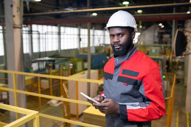 Porträt des selbstbewussten bärtigen schwarzen mannes im schutzhelm unter verwendung des digitalen tabletts in der fabrik