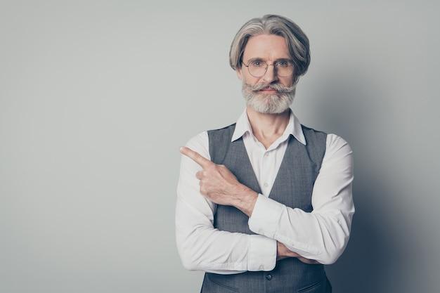 Porträt des selbstbewussten coolen promotors des alten mannes, der mit seinem finger auf eine promotion zeigt